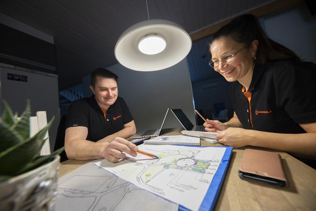 Piha-Suomelan yrittäjät Juha ja Mari Suomela istuvat pöydän ääressä.