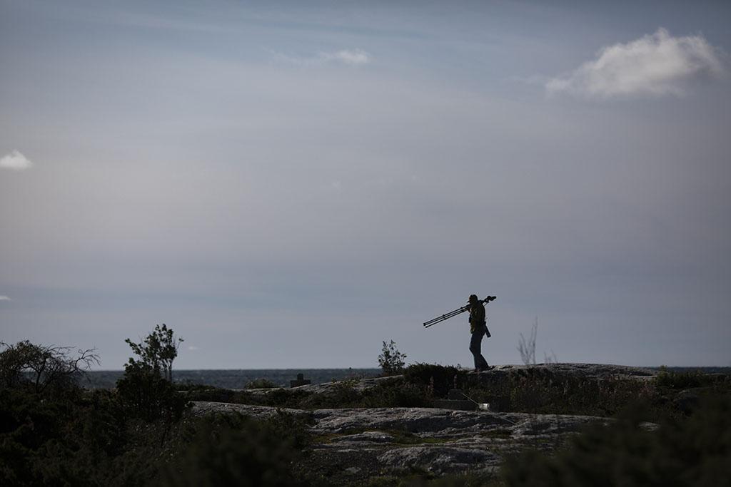 Valokuvaaja kantaa kameraa merellisellä kalliolla.