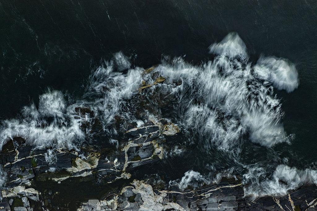 Kallioisia rantoja ja meren aaltoja.