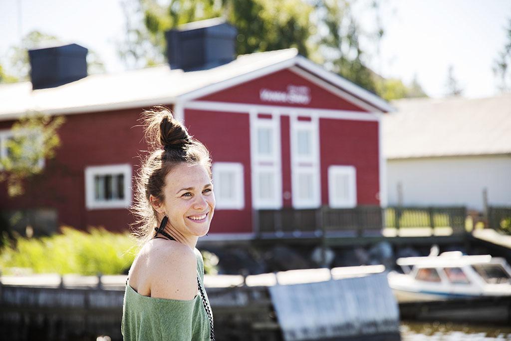Nainen lähikuvassa satamassa, meren rannalla. Taustalla punainen satamarakennus.