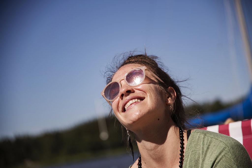 Nainen hymyilee aurinkolasit päässään.
