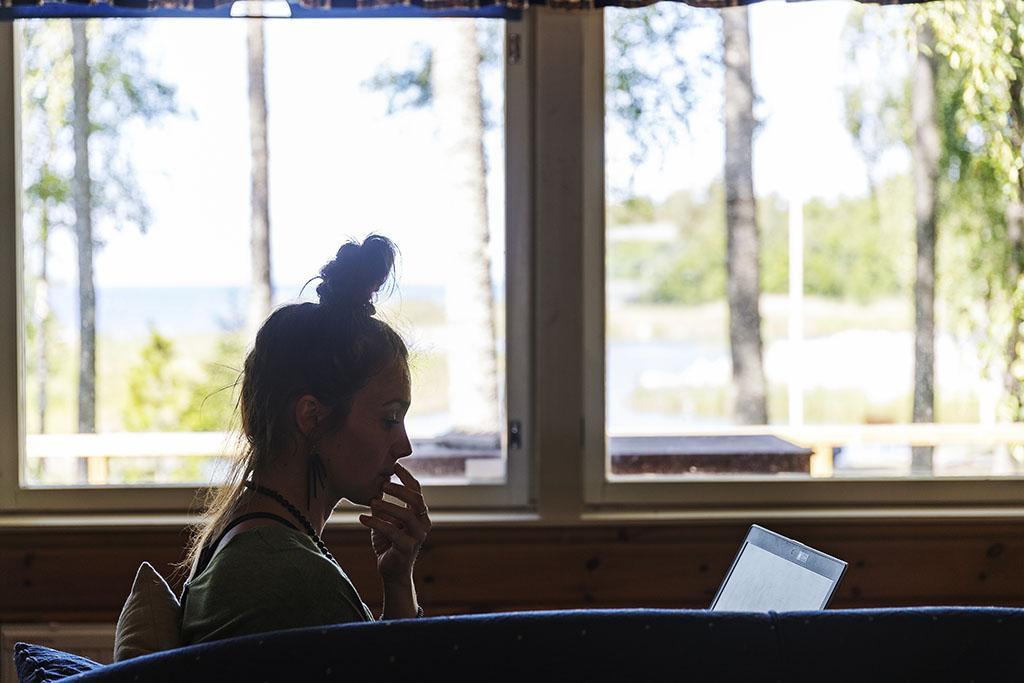 Nainen kannettavalla tietokoneella mökin sohvalla.