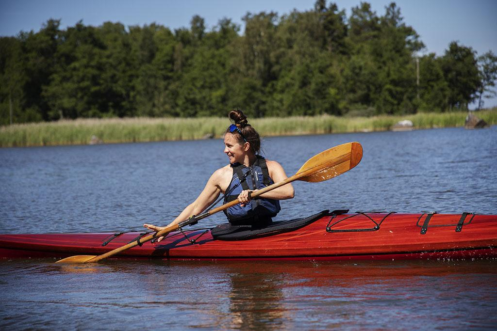 Nainen meloo kanootissa.