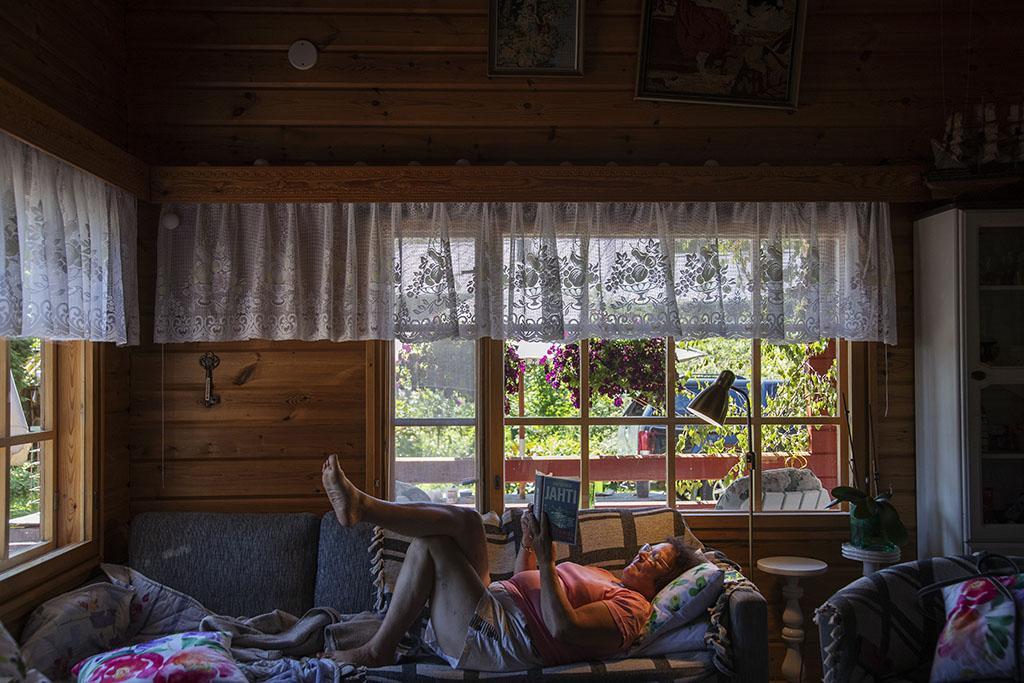 Nainen lukee kirjaa selällään sohvalla.